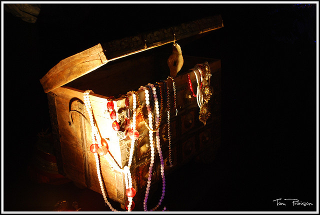 Image of a treasure chest in low light. The lid is open and baubles and strands of beads are draped over the corner.